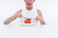 man cuts a tomato at plate