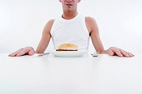 man with burger at plate