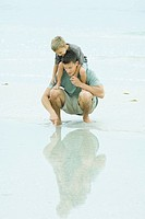 Man crouching at the beach, holding son on shoulders, pointing at shallow water