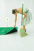 Woman sweeping under rug of artificial turf