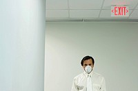 Businessman wearing pollution mask, under exit sign, looking at camera
