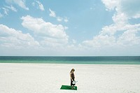 Girl standing on square of artificial turf on beach, holding watering can, high angle view