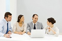 Group of male and female business partners sitting together at table with laptop computer, smiling