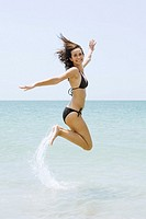 Young woman in bikini at the beach, jumping in the air, smiling at camera