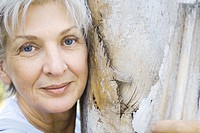 Senior woman leaning against tree trunk, smiling at camera, portrait
