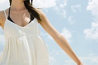 Young woman in sundress outdoors, arms out, cropped view
