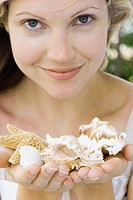 Woman holding up handfuls of seashells, smiling at camera