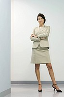 Businesswoman standing with arms folded, smiling, looking away (thumbnail)