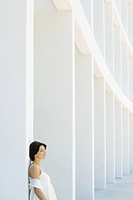 Woman leaning against column with eyes closed, side view (thumbnail)