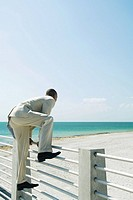 Businessman climbing over fence at the beach, side view