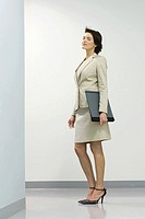Businesswoman standing in hallway with eyes closed, hair tousled by breeze