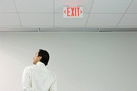 Man standing below exit sign, looking away, rear view