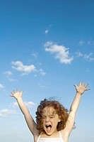 Little girl outdoors with arms raised, open mouth, eyes closed, close-up