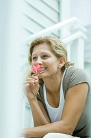 Woman sitting outdoors, smelling flower, looking away
