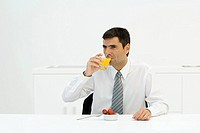 Businessman sitting at table, drinking orange juice, looking away
