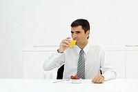 Businessman sitting at table, drinking orange juice, looking away