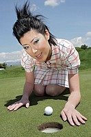 Portrait of a young woman kneeling near a golf hole
