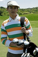 Portrait of a young man carrying a golf bag