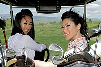 Portrait of two women sitting inside a golf cart