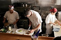 Three people working in kitchen, front view