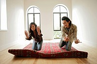 Two people kneeling on carpet, front view