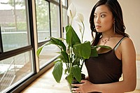Young woman holding potted plant, portrait