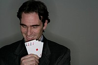 Businessman with four aces, smiling