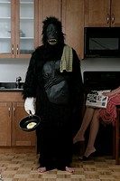 A man in a gorilla costume holds a cooking pan