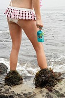 View of a woman at the shore with seaweed shoes