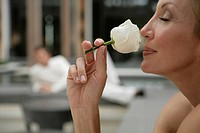 View of a woman smelling a rose (thumbnail)