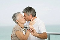 Mature couple kissing on a terrace and taking a picture