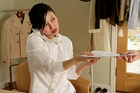 Young woman lending papers, talking on phone
