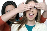 Teenage girl covering hands over other girl's eyes (thumbnail)