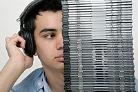 View of a teenage boy behind a pile of cd's listening to music