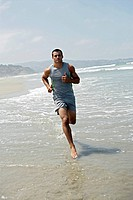 A young man is running on a beach