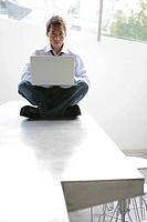 Man sitting in lotus position with a laptop