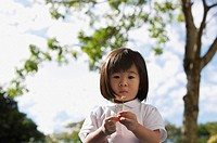 Young girl at park with flower, looking at camera