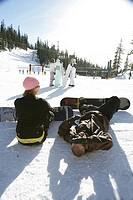 Couple sitting on a ski slope
