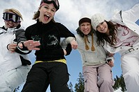 Four Women looking at camera having fun on a ski slope