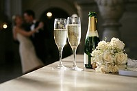 Couple in background of a bottle of champagne