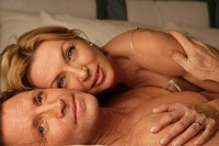 Mature couple in bed smiling (thumbnail)