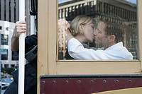 Mature couple kissing on a trolley car (thumbnail)