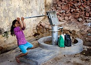 Girl pumping water from well, Allahabad. Uttar Pradesh, India