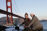 Mature couple on bicycles looking at camear
