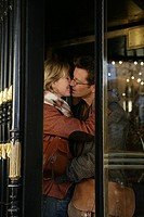 Mature couple kissing inside revolving doors