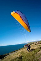 Man with paraglider hang glider taking off  from Constitution hill Aberystwyth over looking  Cardigan bay, Wales UK
