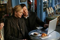 Mature couple outside at a cafe with a laptop