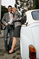 Mature couple leaning against the side of a car