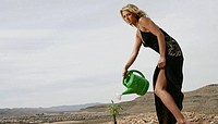 Woman watering a sapling in the desert