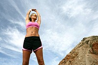 Woman standing outdoors stretching